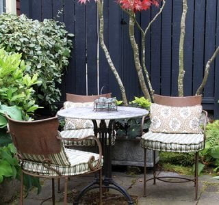 Cozy garden patio with table and chairs.